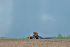 Tractor cultivating the field Stock Images