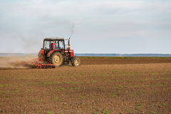 Tractor cultivating field at spring. Stock Photo