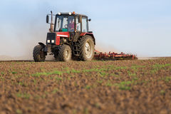 Tractor cultivating field at spring. Royalty Free Stock Image
