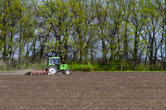 Tractor cultivating field Stock Images