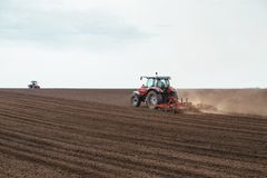 Tractor cultivating field at spring. Agricultural activity Royalty Free Stock Image