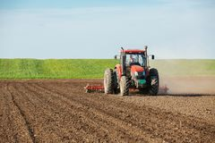 Tractor cultivating field at spring. Agricultural activity Royalty Free Stock Photography