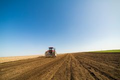 Tractor cultivating field at spring. Agricultural activity Royalty Free Stock Photos