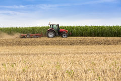 Tractor cultivating wheat stubble field, crop residue.  Royalty Free Stock Photos