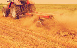 Tractor cultivating wheat stubble field. Crop residue. Photo manipulated to achieve old cross processing xpro look Stock Photo