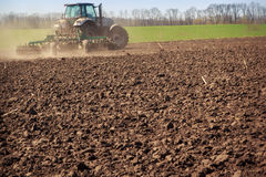 Tractor cultivator raises great dust on soil Royalty Free Stock Photo