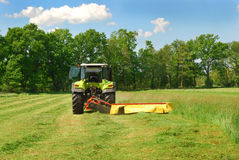 Tractor cutting grass meadow Royalty Free Stock Photos