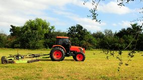 Tractor cutting grass. Tractor pulling a mower and cutting the grass in a South Florida park Stock Photography