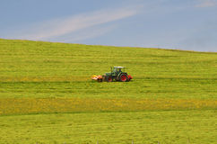 Tractor cutting meadow Stock Photos