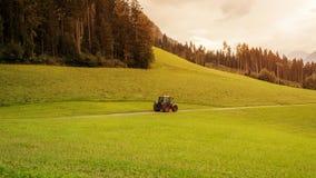 Tractor in de bergen van Zuid-Tirol op de zonsondergang Stock Foto's