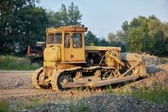Tractor de correa eslabonada amarillo en barranco de la grava Imagen de archivo