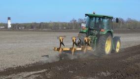 Tractor de cultivo que ara la tierra áspera en campo agrícola antes de sembrar las semillas almacen de video