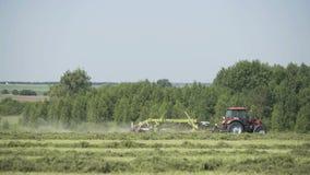 Tractor de cultivo que se mueve en el campo agrícola para cosechar la tierra Maquinaria agrícola en la cosecha del campo almacen de metraje de vídeo