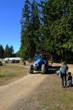 Tractor de granja azul con los árboles verdes grandes en un camino de tierra con el cielo azul foto de archivo