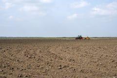 Tractor de granja rojo que prepara la tierra para sembrar imagenes de archivo