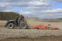 Tractor de granja y cultivador en campo de la primavera foto de archivo