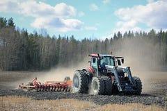 Tractor de granja y cultivador en campo en la primavera imagen de archivo libre de regalías