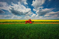 Tractor in de landbouwgebieden en de dramatische wolken stock fotografie