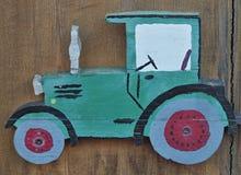 Tractor de madera lindo en una puerta de madera imagen de archivo libre de regalías