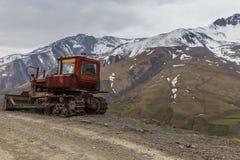 Tractor de oruga soviético viejo en el fondo de coronado de nieve Fotografía de archivo libre de regalías