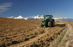 Tractor debajo de las montañas fotografía de archivo libre de regalías