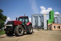 Tractor delante de silos Foto de archivo libre de regalías