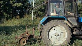 Tractor die aan het aardappelgebied werken Oogstend aardappels met het gebruiken van tractor Stock Afbeelding