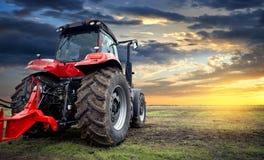 Tractor die aan het landbouwbedrijf, een modern landbouwvervoer die, een landbouwer werken op het gebied, tractor bij zonsonderga royalty-vrije stock afbeeldingen
