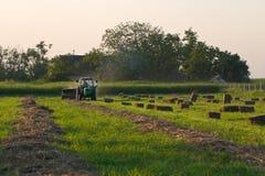 Tractor die de balen van het Hooi maakt Stock Afbeeldingen