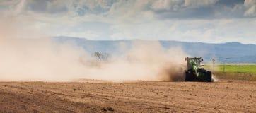 Tractor die droge landbouwgrond ploegen royalty-vrije stock fotografie