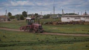 Tractor die een gebied naast een dorpslandbouwbedrijf ploegen stock footage
