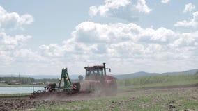 Tractor die een gebied op een mooie dag ploegen stock videobeelden