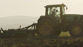 Tractor die een groen gebied in langzame motie cultiveren stock videobeelden