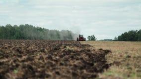 Tractor die gebied cultiveren bij de lente stock footage