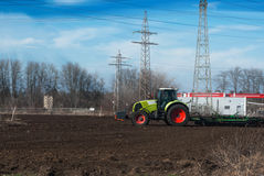 Tractor die gebiedsgrond voor het zaaien in de lente voorbereiden Onderbrekingen B stock fotografie