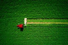 Tractor die groen landbouwgebied, luchthommelmening maaien stock fotografie