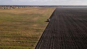 Tractor die het gebied ploegt De mening van het vogel` s oog royalty-vrije stock fotografie
