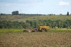 Tractor die het gebied ploegt Landelijk landschap Stock Afbeeldingen