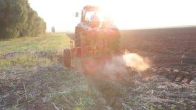 Tractor die het zwarte gebied van de aardeploeg ploegen bij zonsondergang stock video
