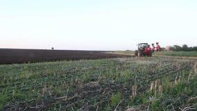 Tractor die het zwarte gebied van de aardeploeg ploegen bij zonsondergang stock footage