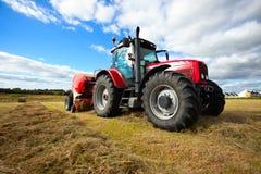 Tractor die hooiberg op het gebied verzamelt Stock Afbeeldingen