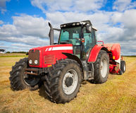 Tractor die hooiberg op het gebied verzamelt Royalty-vrije Stock Afbeeldingen