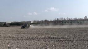 Tractor die die op de gebieden werken, door een lopende trein worden bereikt stock video