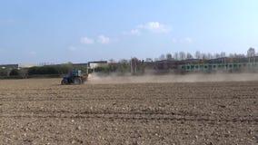 Tractor die die op de gebieden werken, door een lopende trein worden bereikt stock videobeelden