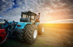 Tractor die op het gebied op de achtergrond van de zonsondergang werken royalty-vrije stock afbeeldingen