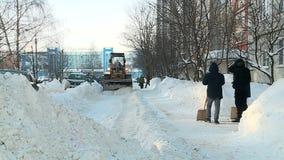 Tractor die sneeuw in de yard in Rusland in de winter harken stock footage