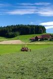 Tractor die zich naast gemaaid gras bevindt Stock Foto's