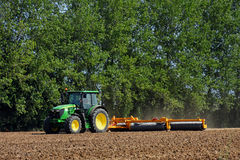 Tractor with Disc Harrow in Field Stock Photo