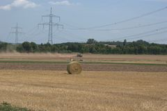 Tractor in the distance, harrowing a field after the summer harvest and throwing up dust clouds, with a bales of straw in the fore. Tractor in the distance Stock Image