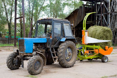 Tractor drawn machine for packing hay Royalty Free Stock Photos